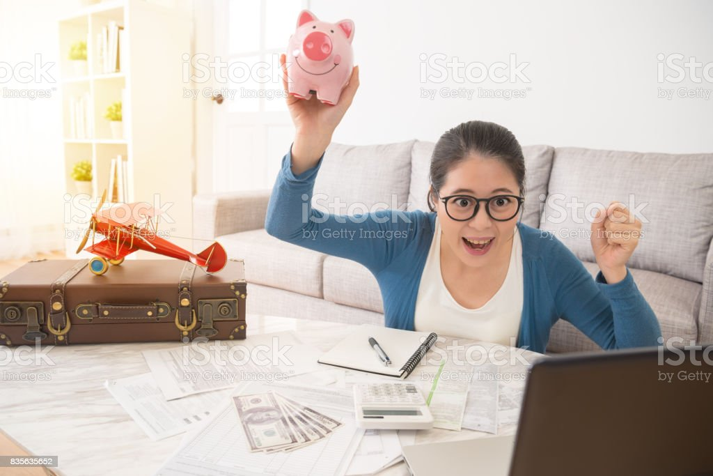 woman happy to pick up the pink piggybank stock photo