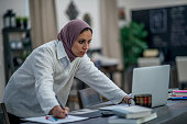 A Middle-eastern woman is indoors in her home office. She is wearing a head scarf. She is standing an looking at her laptop while writing on paper.