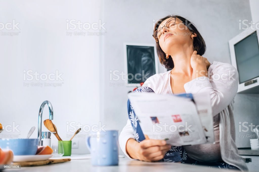 Woman has a neck pain when reads a magazine on the kitchen at morning time royalty-free stock photo