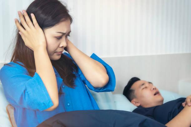 Eine Frau hat ein Ärgernis für den Mann er liebt schlafen lautes Schnarchen. Konzept des Zusammenlebens – Foto