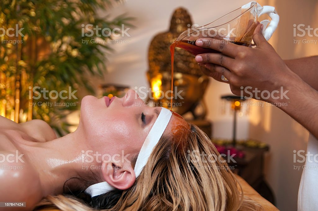 A woman has a soothing Ayurveda massage to her forehead  stock photo