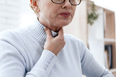 istock A woman has a sore throat. 1289371396