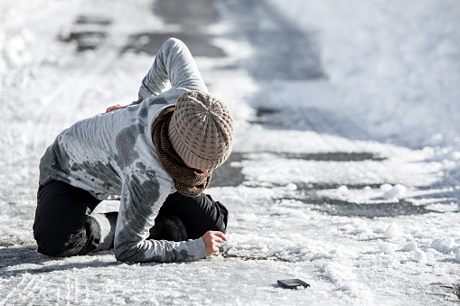 Woman has an accident cause of black ice on the road, downfall and injury, copyspace