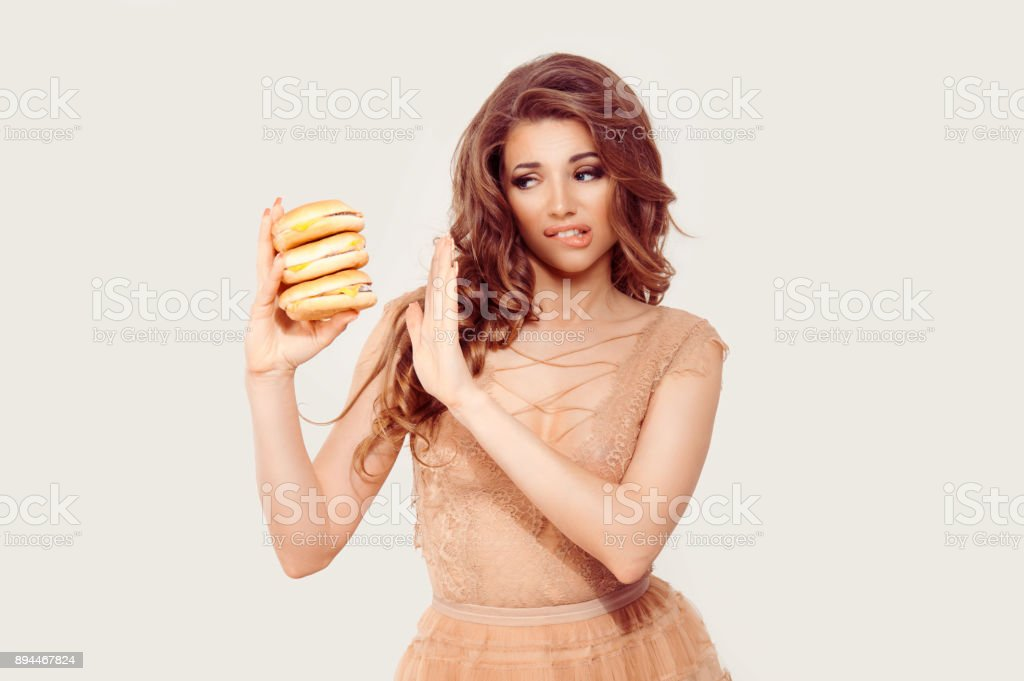 Woman has craving for fast food in her hand, she is hardly abstaining avoiding to eat it, gesturing stop no with other hand isolated white background. stock photo