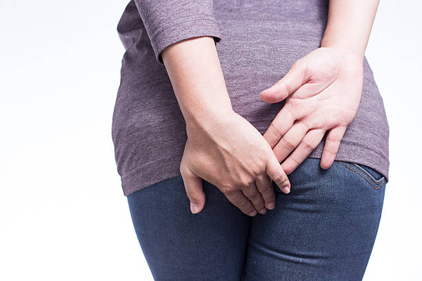 Woman Has Diarrhea Holding Her Butt on Isolated White Background stock photo