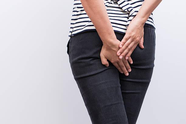Woman has diarrhea holding her butt stock photo