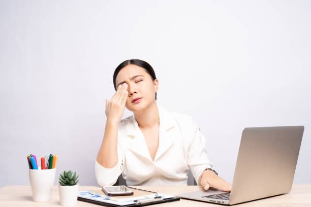 Woman has eyes pain at office isolated over white background stock photo