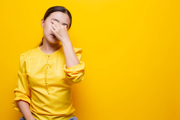 Woman has eyes pain isolated over yellow background stock photo