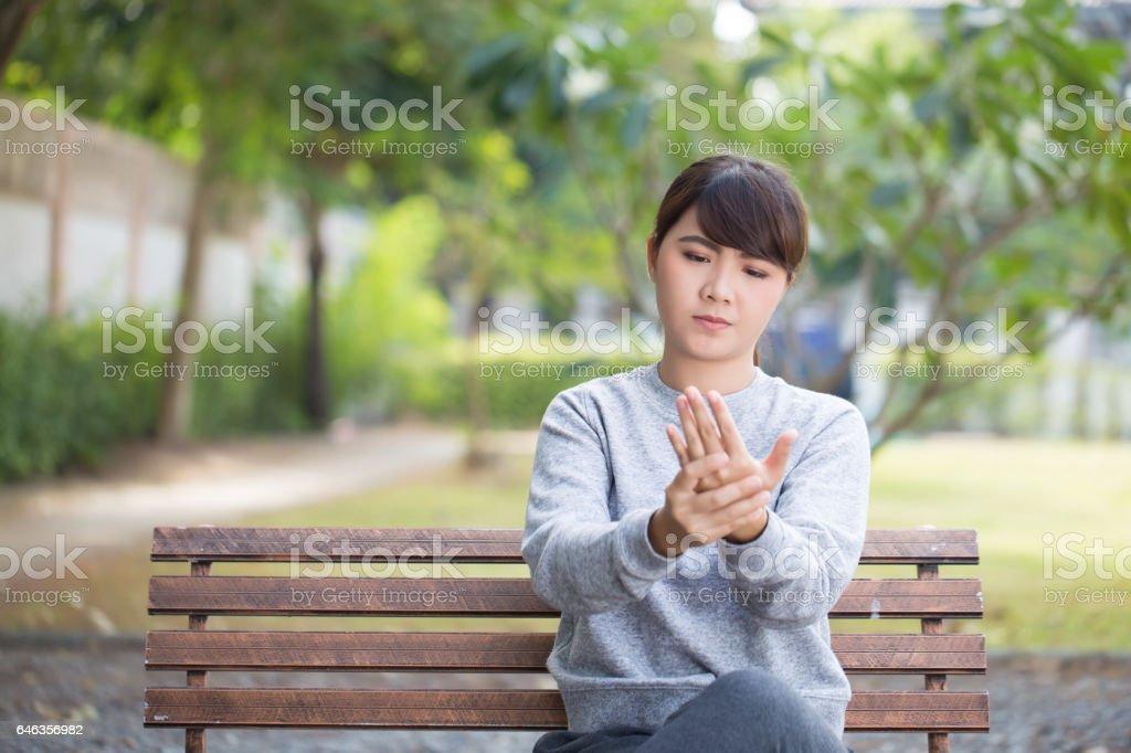 Woman has hand pain at park stock photo