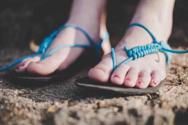 frau hat handgefertigte sandalen. sandalen von gummi- und saiten. detail des fußes. - flip flops reparieren stock-fotos und bilder