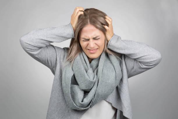 Frau hat Kopfschmerzen und hält ihren Kopf – Foto