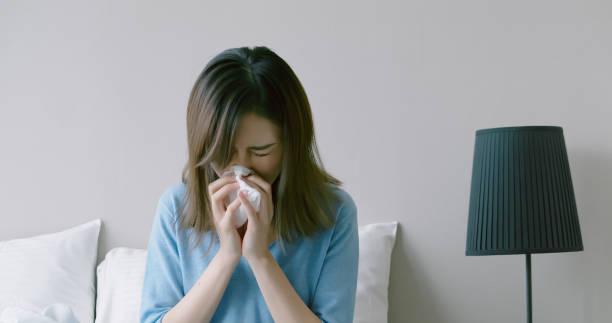 女性は鼻を出している - くしゃみ 日本人 ストックフォトと画像