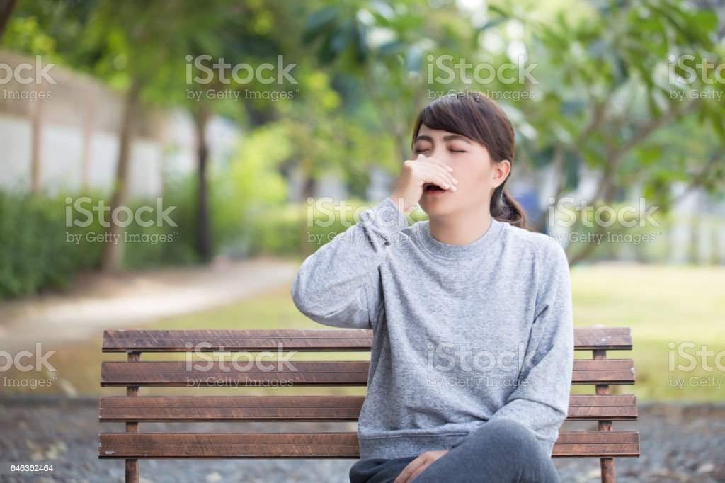 Woman has sneezing at park stock photo