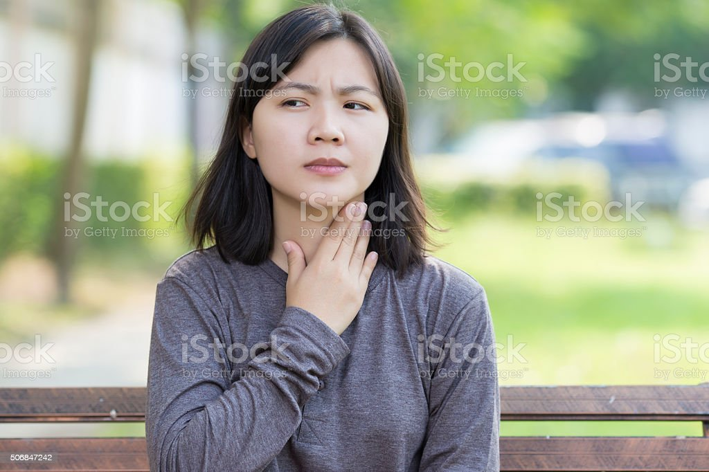 Woman has Sore Throat at Park stock photo