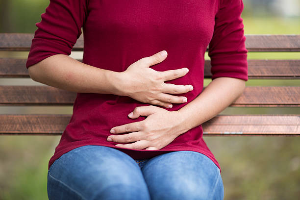 woman has stomach ache sitting on bench at park - human digestive system stock pictures, royalty-free photos & images