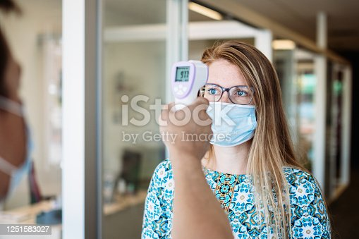 A pandemic workplace environment.  Office workers wear face coverings to protect the spread of virus doing the Covid-19 / Coronavirus outbreak.  Body temperature is checked with a infrared thermometer.  Shot in Washington State, USA.