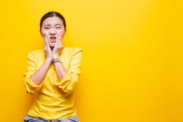 Woman has toothache isolated over yellow background stock photo