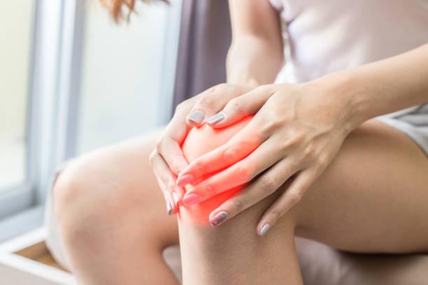 kvinnan har en knäskål smärta sitter på sängen i sovrummet efter vakna upp och känna så sjukdom, hälso-och koncept - knäskål bildbanksfoton och bilder