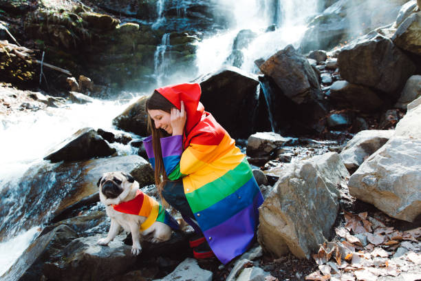 Woman have a lovely time with her dog at the waterfall Young woman with long hair and her small cute dog - pug breed in colorful raincoats enjoying the sunny fresh spring day at the waterfall in Carpathian Mountains, Ukraine dog and person raincoat stock pictures, royalty-free photos & images