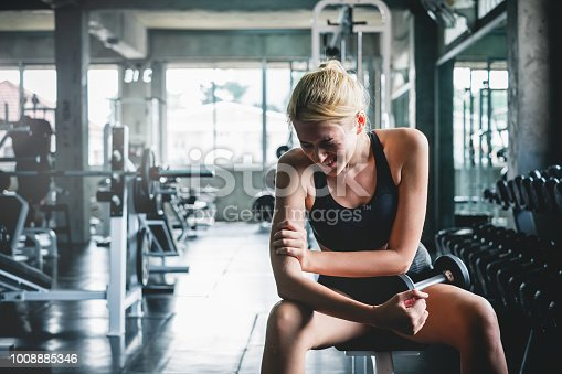 istock Woman have accident injury and hurt at arms while workout and weight training at gym, muscle pain concept 1008885346