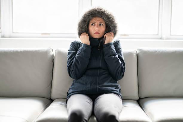 女人在家裡的沙發上穿著冬衣很冷 - 寒冷的 個照片及圖片檔