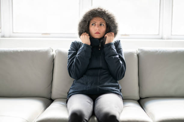 Woman have cold on the sofa at home with winter coat A woman have cold on the sofa at home with winter coat warm clothing stock pictures, royalty-free photos & images
