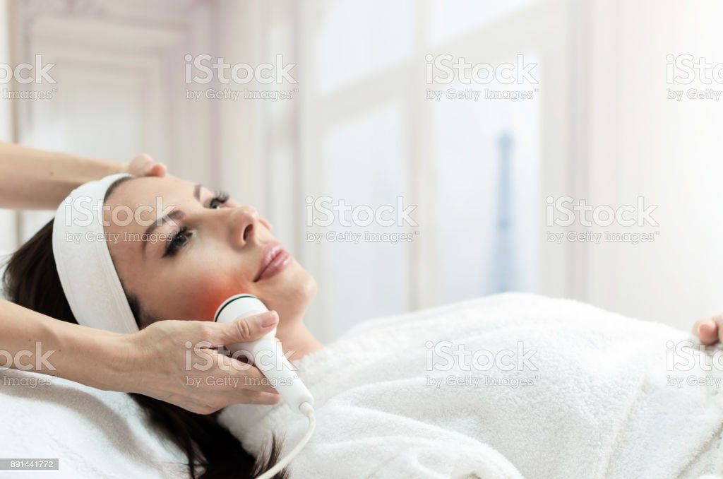 Woman have facial laser treatment in beauty spa, Paris in background stock photo