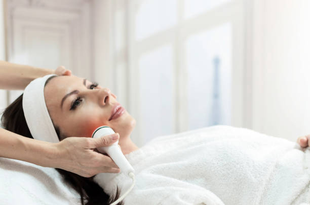 Woman have facial laser treatment in beauty spa, Paris in background Beautiful woman getting laser and ultrasound face treatment in medical spa center, skin rejuvenation concept tighten stock pictures, royalty-free photos & images
