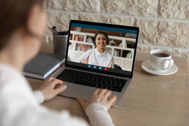 Woman have webcam lesson with ethnic teacher stock photo