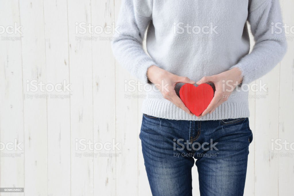 Woman havinbg herat shape on lower stocmach stock photo