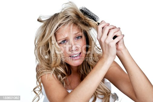 Woman with upset expression trying to get a brush out of her hair