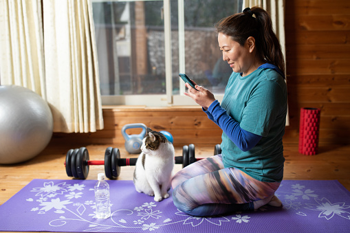 Woman having a break from her exercise to check phone with her cat