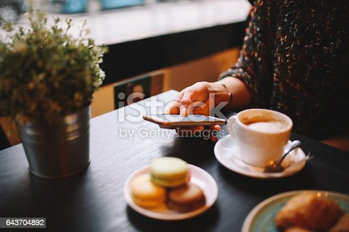 Vintage toned image of a young woman sitting in the cafe, having espresso coffee, French croissants and some sweet macarons. Relaxing and enjoying the moment in the afternoon, she is taking a photograph of the foods and coffee with her smart phone.