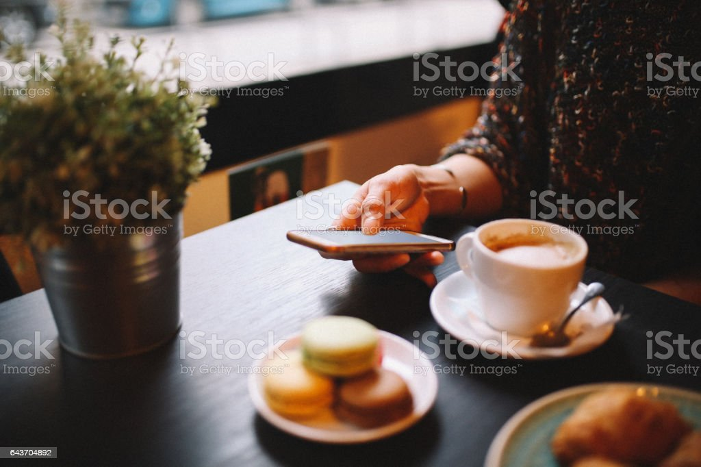 Woman having a coffee and sweets in the cafe stock photo