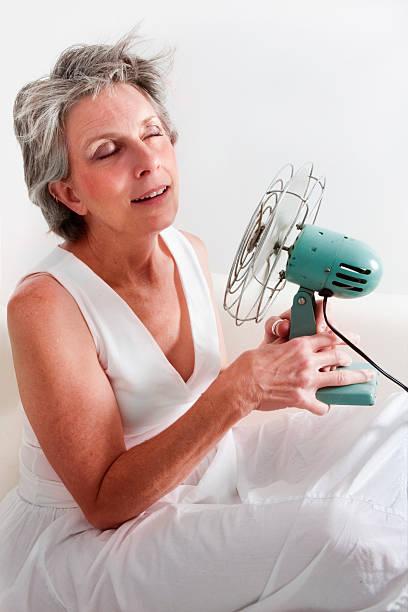 woman having a hot flash stock photo