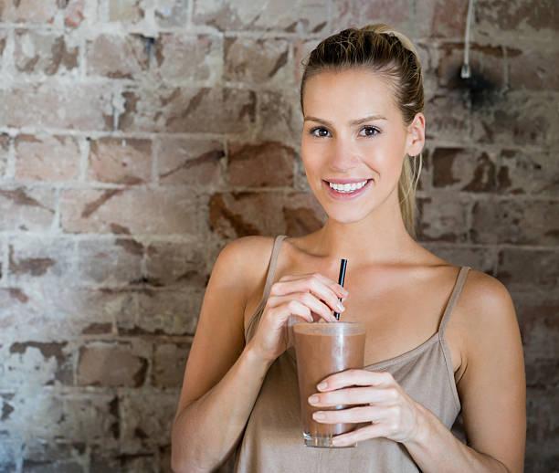 woman having a milkshake - diät shakes stock-fotos und bilder