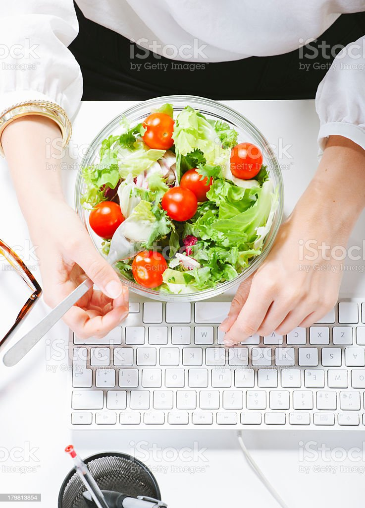 Woman having a salad lunch whilst sat at her computer  stock photo
