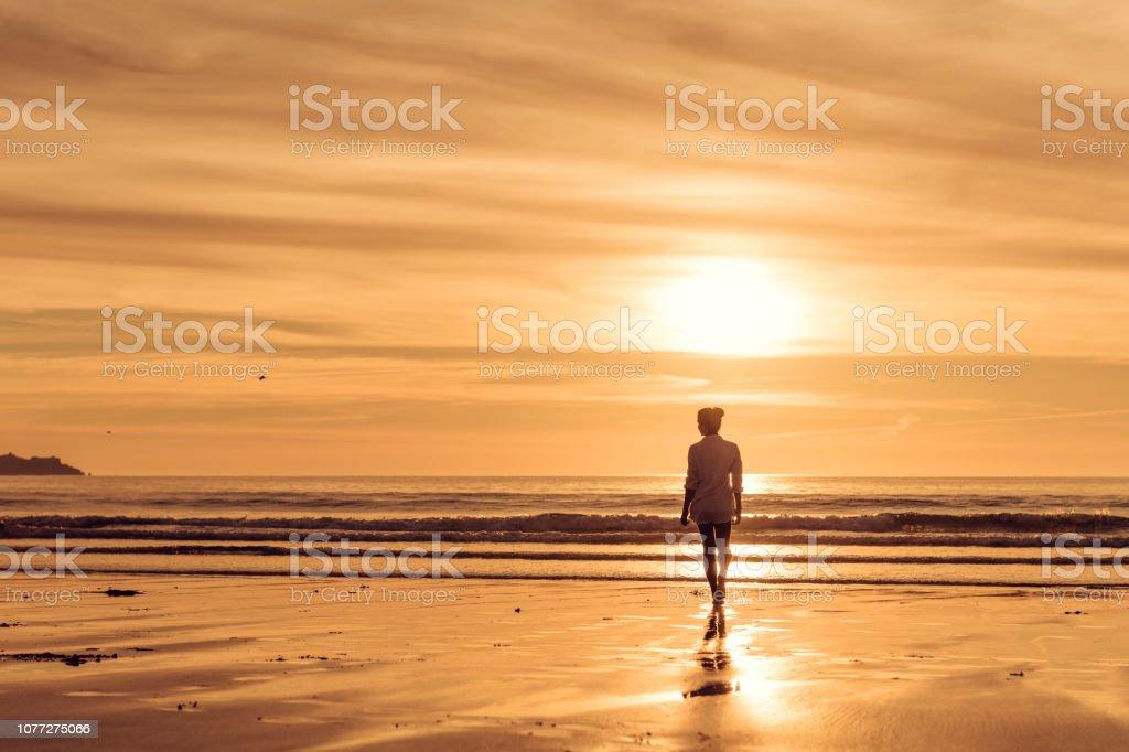 Woman having a sunset walk along Gwithian Towans Beach on a June evening. stock photo