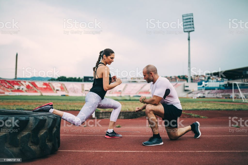 Young woman exercising with a personal trainer at the running track