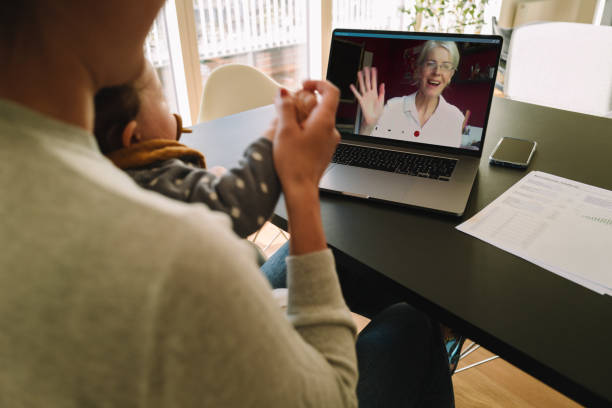 Woman having a video call with her mother Woman with her daughter having video call with her mother. Woman connecting with her mother on a video call while at home. jacoblund stock pictures, royalty-free photos & images