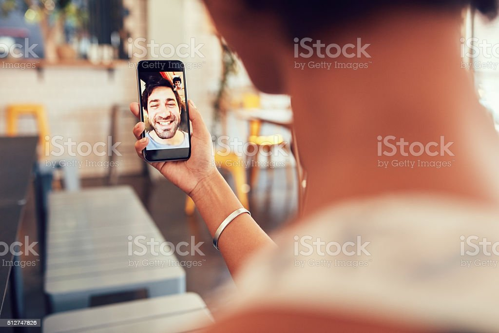 Woman having a video call with man on her phone stock photo