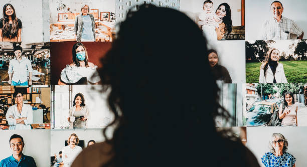 Woman having a video conference at home with a big screen stock photo