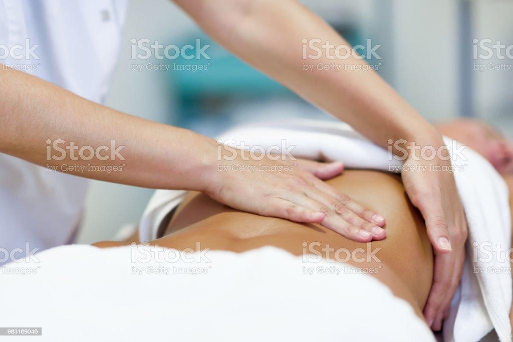 Woman having abdomen massage by professional osteopathy therapist stock photo
