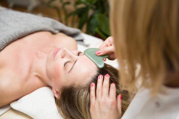 Woman having an gua sha facial massage with natural jade stone massager stock photo