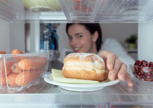 woman having an unhealthy snack - cravings bildbanksfoton och bilder