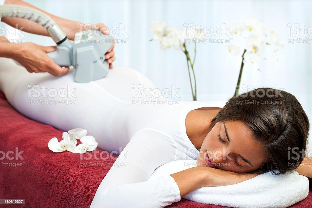 Woman having anti cellulite vibro massage. stock photo