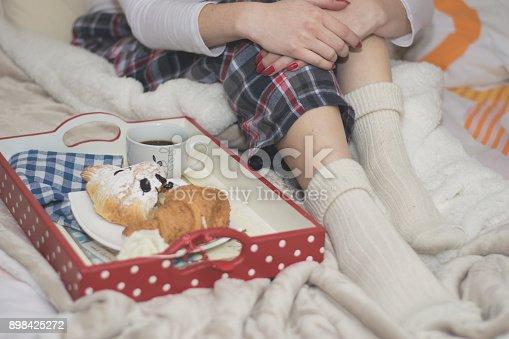 618750646istockphoto Woman having breakfast in bed 898425272