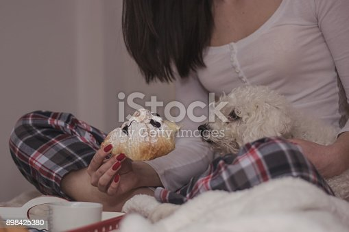 618750646istockphoto Woman having breakfast in bed 898425380