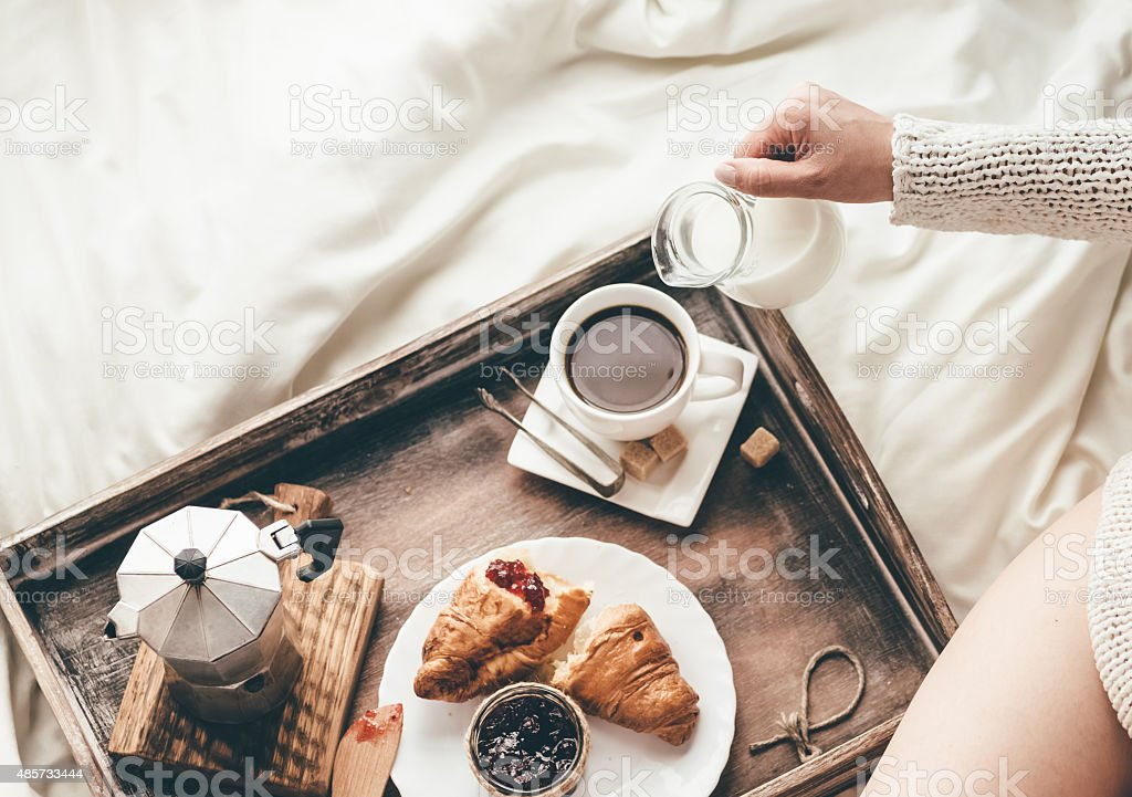 Woman having breakfast in bed. Window light stock photo