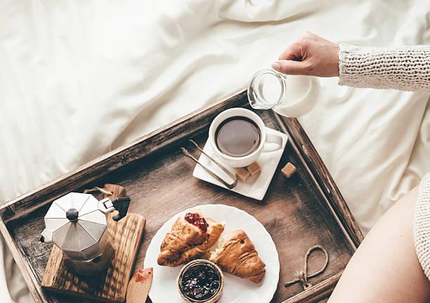 Woman having breakfast in bed. Window light stock photo